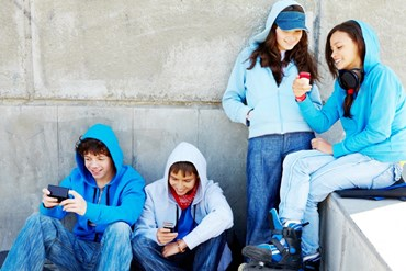Four teenagers with cellphones in a stair.