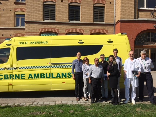 Group of people in front an ambulance car outside a hospital building